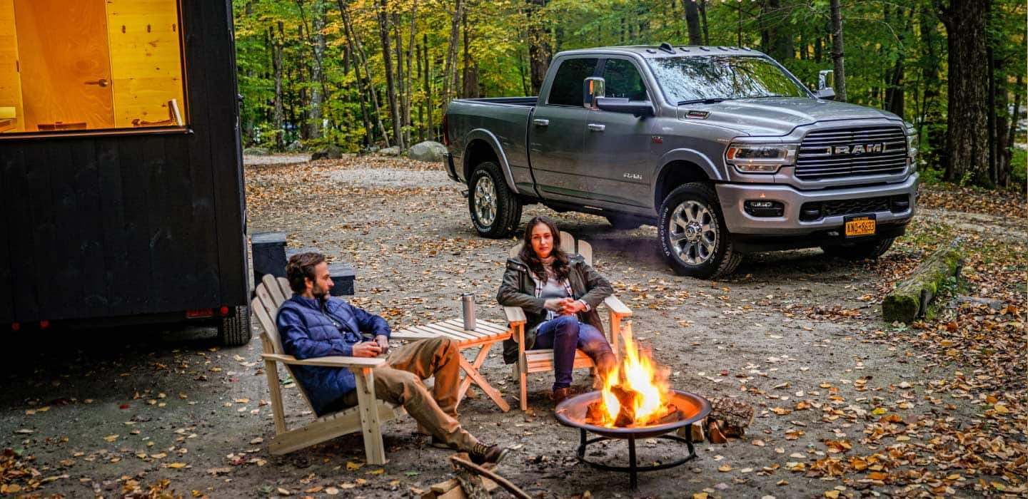 Display A couple in camping chairs outside a tiny house with a 2019 Ram 2500 Laramie in the background.