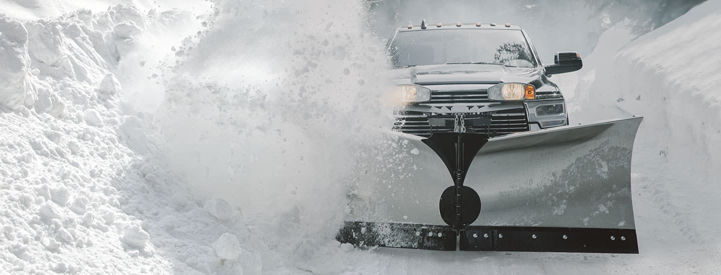 A head-on view of a 2020 Ram 2500 Laramie Crew Cab with a large stainless steel V-style plow attachment, being driven through a massive amount of snow.