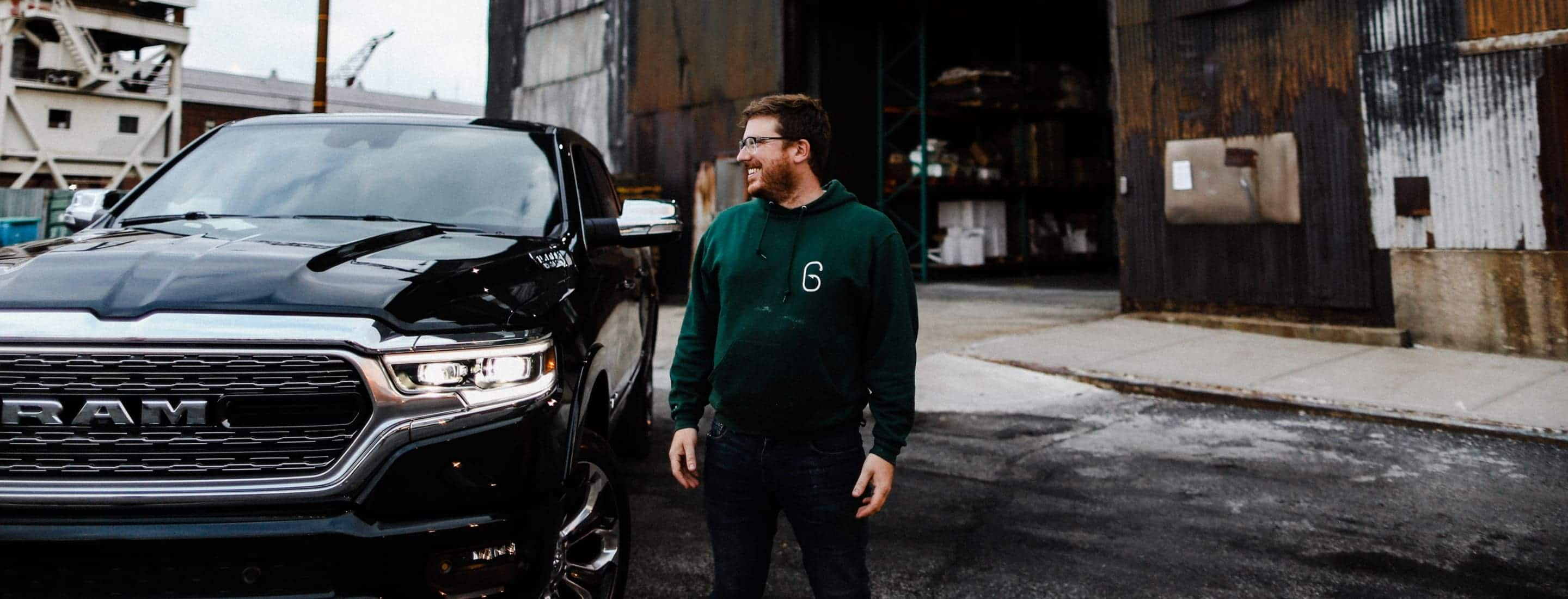 A man smiling broadly as he stands next to his 2019 Ram 1500 Limited.