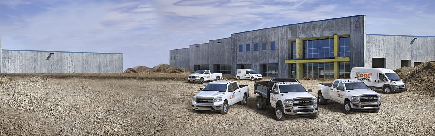Six Ram vehicles including the Ram ProMaster City, Ram 1500 Classic, Ram 1500, Ram Chassis Cab, Ram 3500, and Ram ProMaster parked side by side at a construction site.