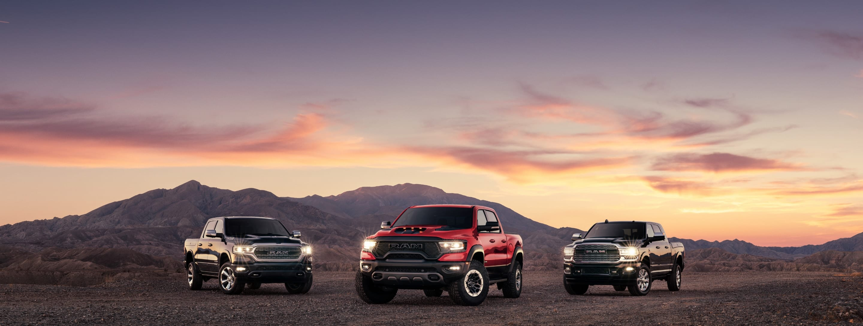 Three 2021 Ram trucks parked on a mountain trail—a Ram 1500 Limited, Ram 1500 TRX and Ram 2500 Limited.