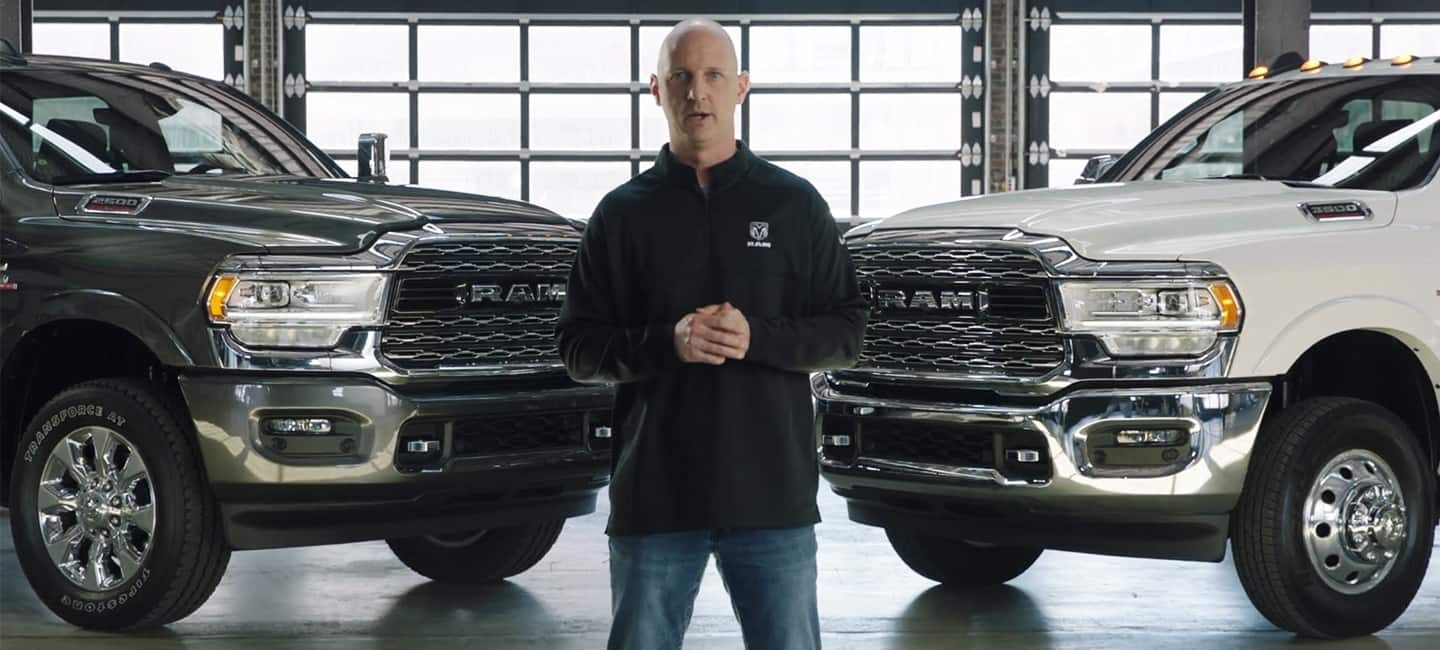 A man stands in front of two 2019 Ram Heavy Duty trucks.